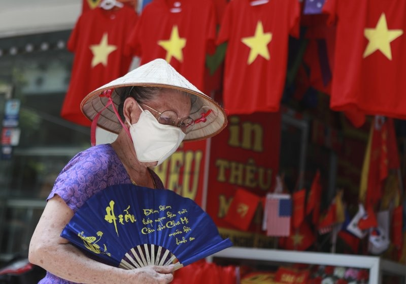 Woman walks past row of T-shirts printed with Vietnamese flags in Hanoi.