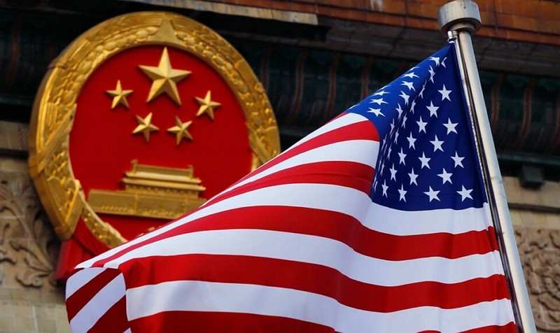 An American flag is flown next to the Chinese national emblem outside the Great Hall of the People in Beijing.