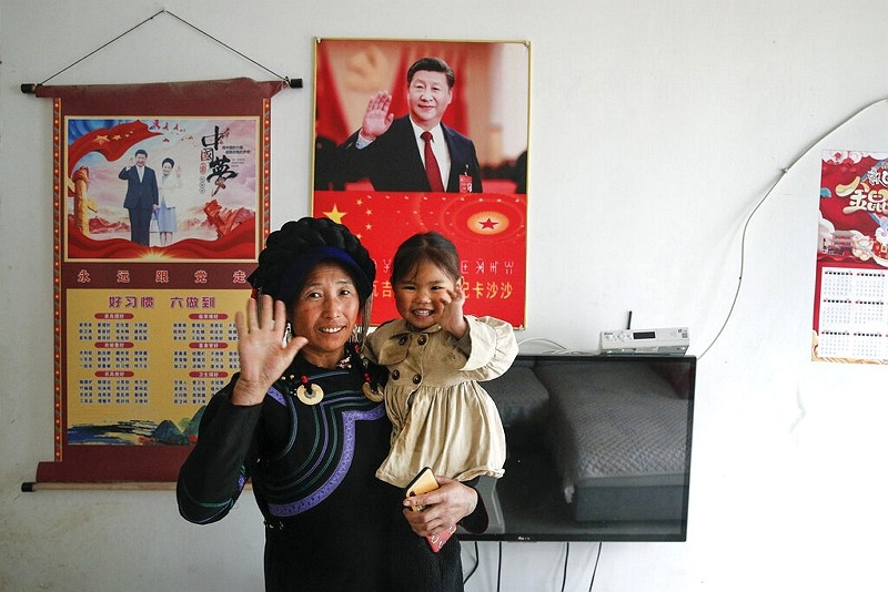 A minority woman and a child wave near posters showing images of Xi Jinping and his wife Peng Liyuan on display on a wall.