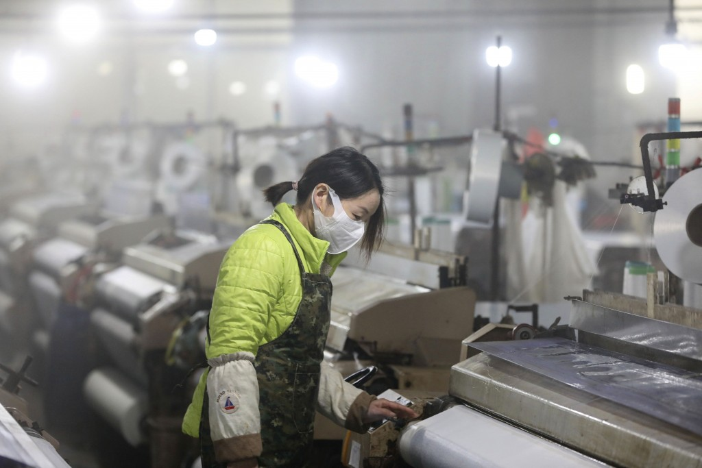 In this Feb. 27, 2020 photo, a woman works on a spinning mill in a textile factory in Hangzhou in eastern China's Zhejiang Province.