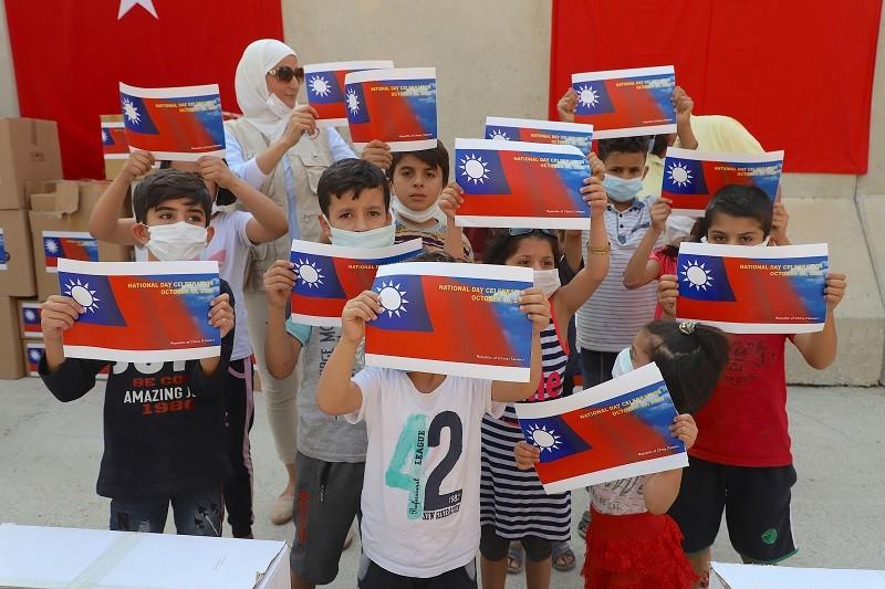土耳其、敘利亞邊界台灣-雷伊漢勒世界公民中心建築主體完工。9日揭幕前,家住台灣中心附近的敘利亞兒童手持列印的中華民國國旗合照。中央社