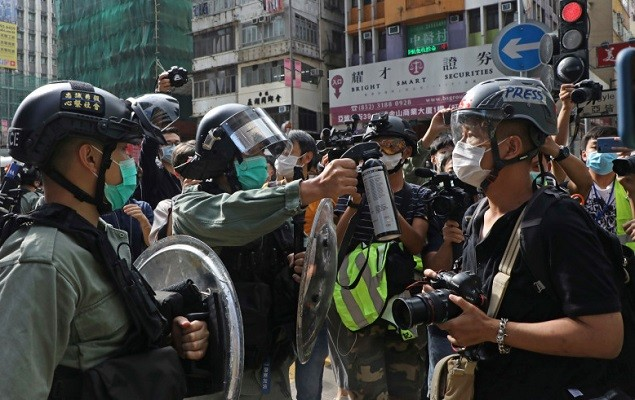 Riot police aim pepper spray at journalists as pro-democracy activists gather outside a mall in Hong Kong on May 1, 2020.