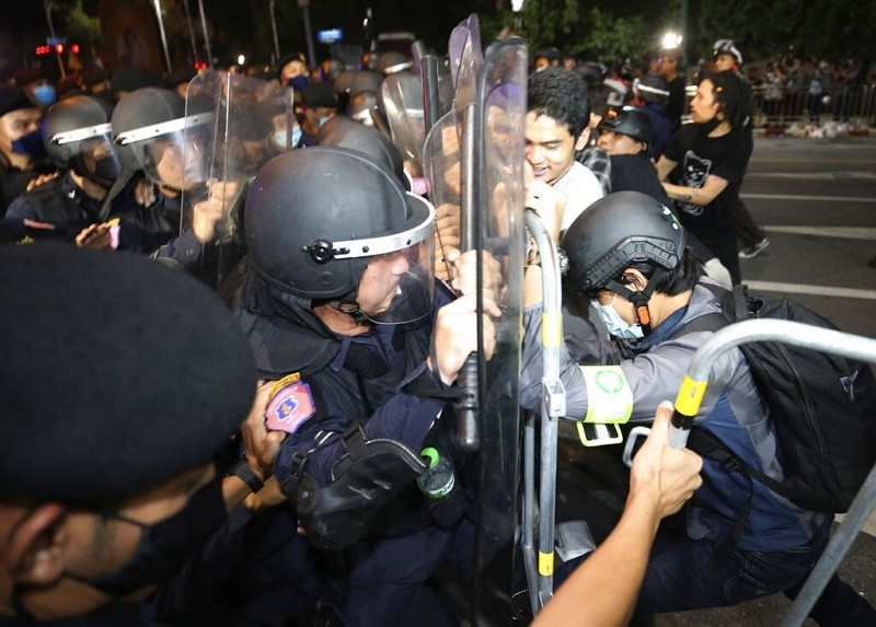 Pro-democracy protesters push Thai policemen with riot shields during a demonstration in Bangkok, Oct. 15.