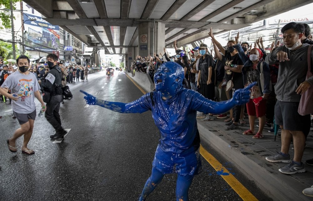 A pro-democracy protester covered in blue paint gestures on a road during a protest in Udom Suk, suburbs of Bangkok, Thailand, Saturday, Oct. 17, 2020...