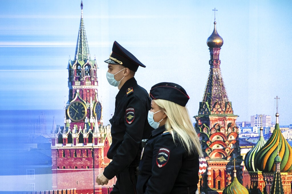 Police officers walk pastphoto of Kremlin's Spasskaya Tower, left, and St. Basil's Cathedral in Sheremetyevo Airport.