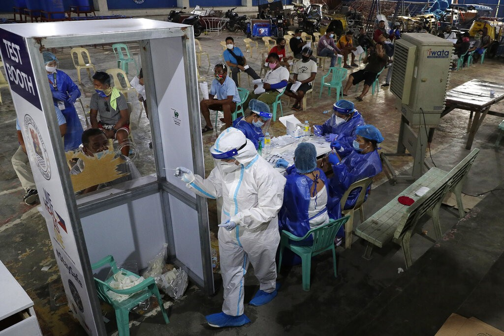 Health workers in protective suits prepare to administer free COVID-19 tests in low-income area in Manila, Philippines.