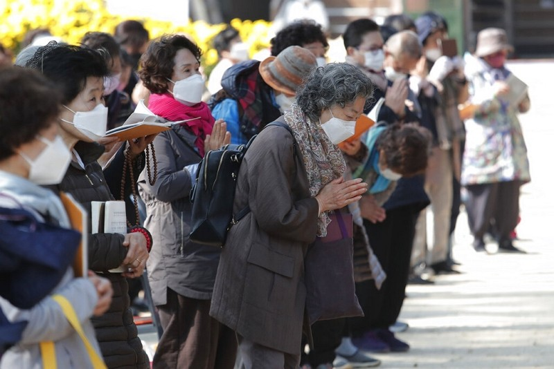 People wearing face masks pray during a service at the Chogyesa temple in Seoul, South Korea, Oct. 19.