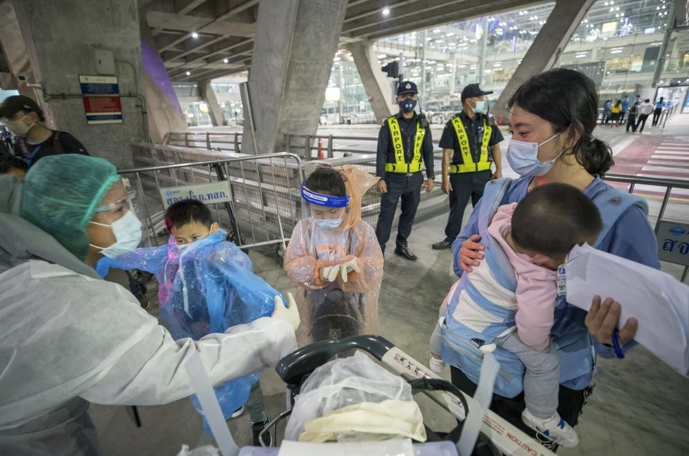 A health worker (left) helping Chinese visitors from Shanghai arriving at Bangkok's Suvarnabhumi Airport Oct. 20