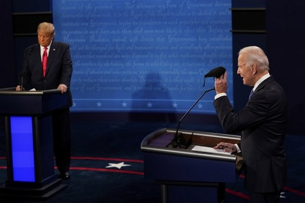 Democratic presidential candidate former Vice President Joe Biden holds up a mask as President Donald Trump takes notes during the second and final pr...