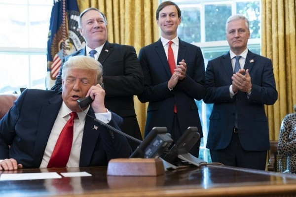 U.S. President Donald Trump talks on a phone call with the leaders of Sudan and Israel in the Oval Office of the White House.