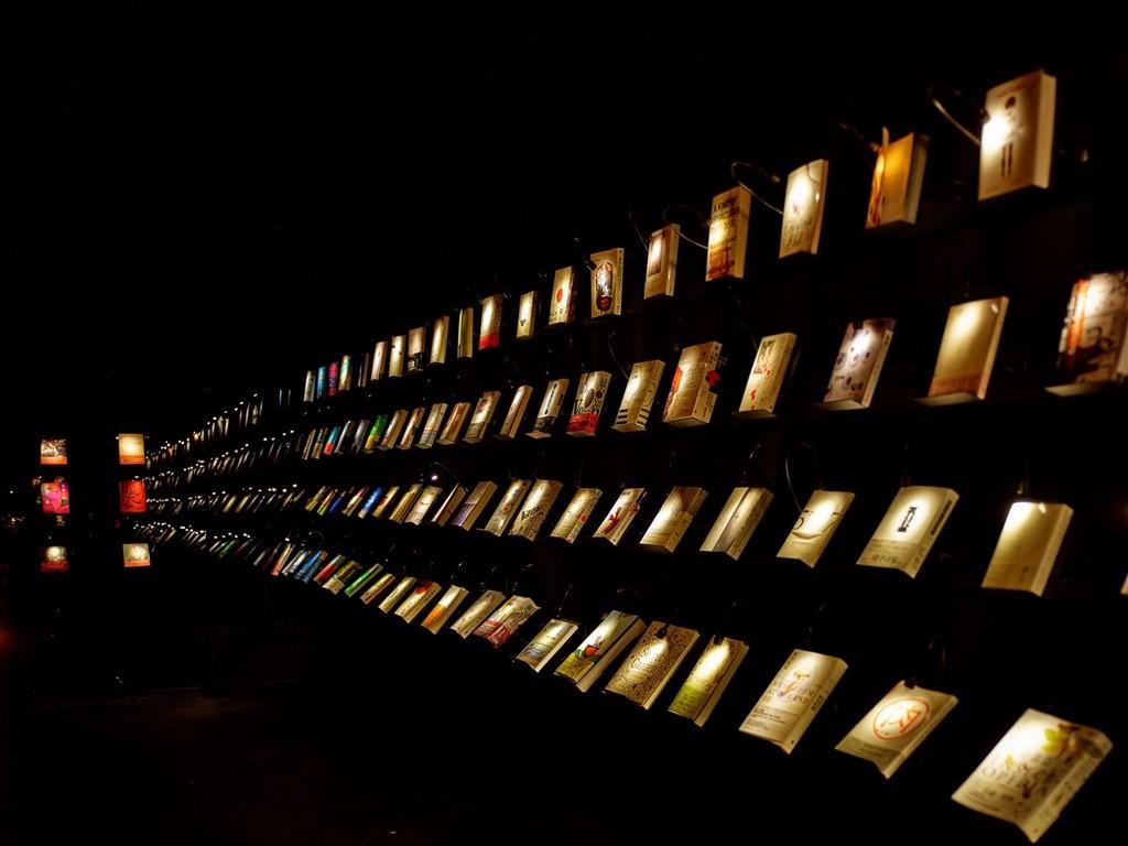位於高雄駁二藝術特區的「無關實驗書店」打造一片漆黑的空間,微光只打在每本書和幾張閱讀桌上。(圖取自facebook.com/wuguanb...