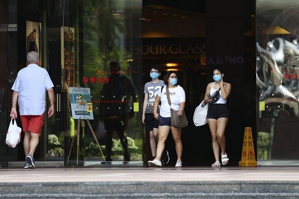 People wearing protective face masks exit mall along the Orchard Road shopping belt in Singapore.