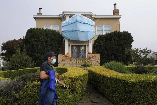 A man walks past a large face mask hanging over pumpkins in front of a house during the coronavirus pandemic in San Francisco.