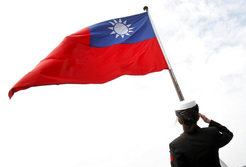 Taiwanese officer salutes national flag.