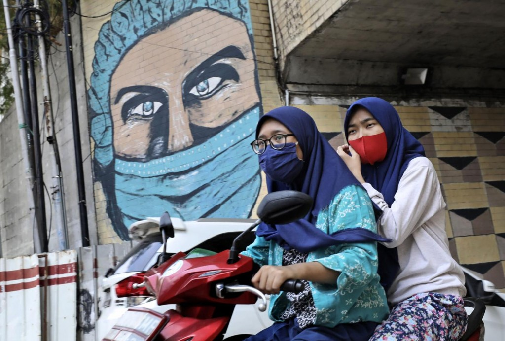 Women wearing masks ride motorbike past large COVID-19-themed mural in Jakarta, Indonesia, Friday, Oct. 2, 2020.