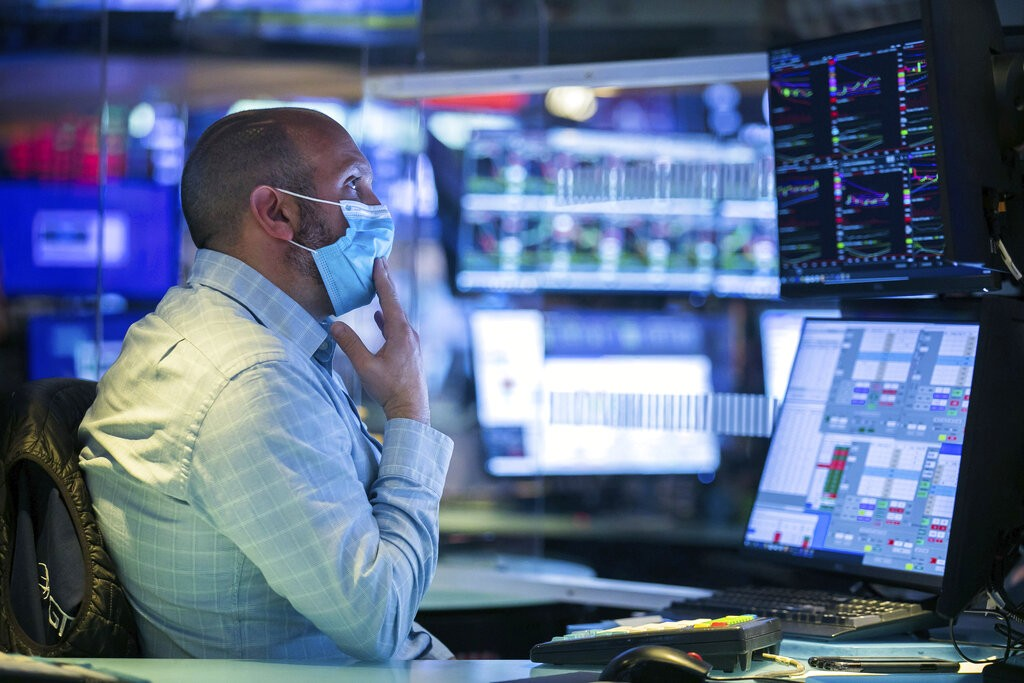 In this photo provided by the New York Stock Exchange, specialist James Denaro works at his post on the trading floor, Wednesday Oct. 28, 2020. The Do...