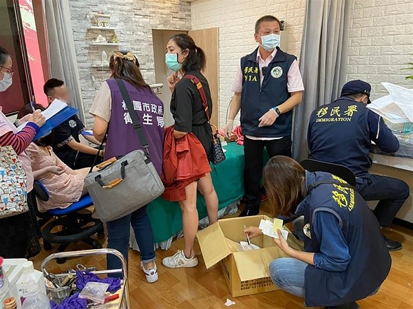 NIA officials conduct a search at the Vietnamese woman's work studio. (NIA photo)