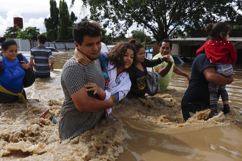 People wading through the streets of Jerusalen, Honduras, following Hurricane Eta