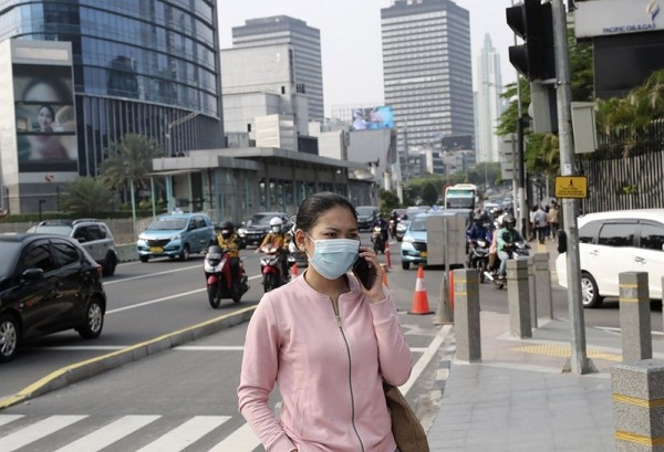 A woman, wearing a face mask as a precaution against the new coronavirus outbreak, talks on her mobile phone on the sidewalk of a street at the main b...