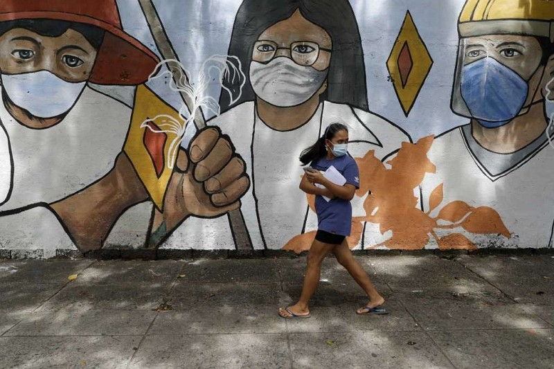A woman wearing protective mask to prevent the spread of the coronavirus walk past a muralin Manila, Philippines.
