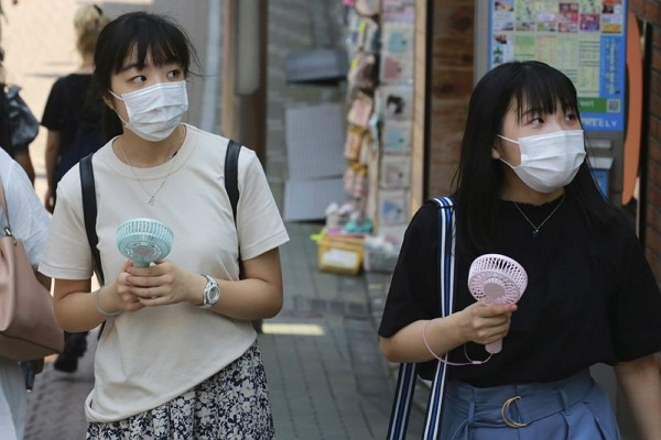 People wearing face masks to help protect against the spread of the coronavirus hold portable fans to cool themselves in the heat in Tokyo.