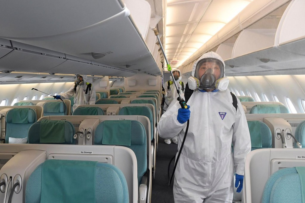 Stock image of workers spraying disinfectant in aircraft cabin.