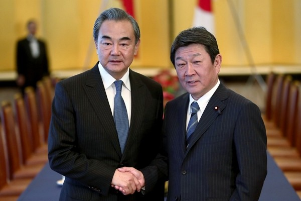 In this Nov. 25, 2019, file photo, Chinese Foreign Minister Wang Yi, left, poses with his Japanese counterpart Toshimitsu Motegi for a photo prior to ...