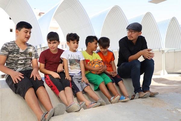 Taiwanese architect Chiu Chen-yu shares a moment with children inReyhanli.