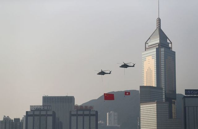 Helicopters carrying China's national flag and Hong Kong's flag fly past the skyline of Victoria Harbour on China's National Day, 2019. (R...