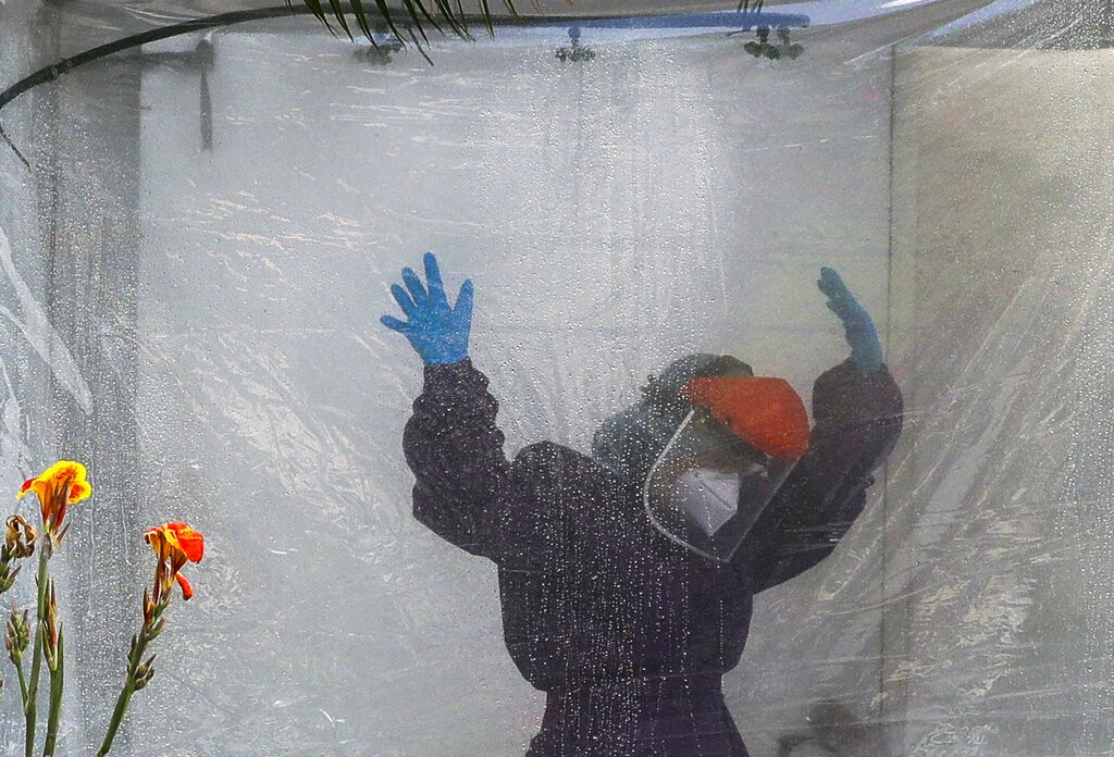 Health worker wearingprotective suit is disinfected inportable tent outside Gat Andres Bonifacio Memorial Medical Center in Manila, Philip...