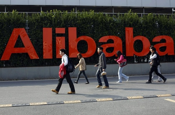 People walk past a company logo at the Alibaba Group headquarters in Hangzhou, in eastern China's Zhejiang province.