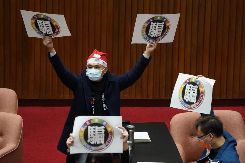 民進黨立委在廣泛討論發言時,國民黨立委陳以信(後)等人舉出標語抗議。中央社