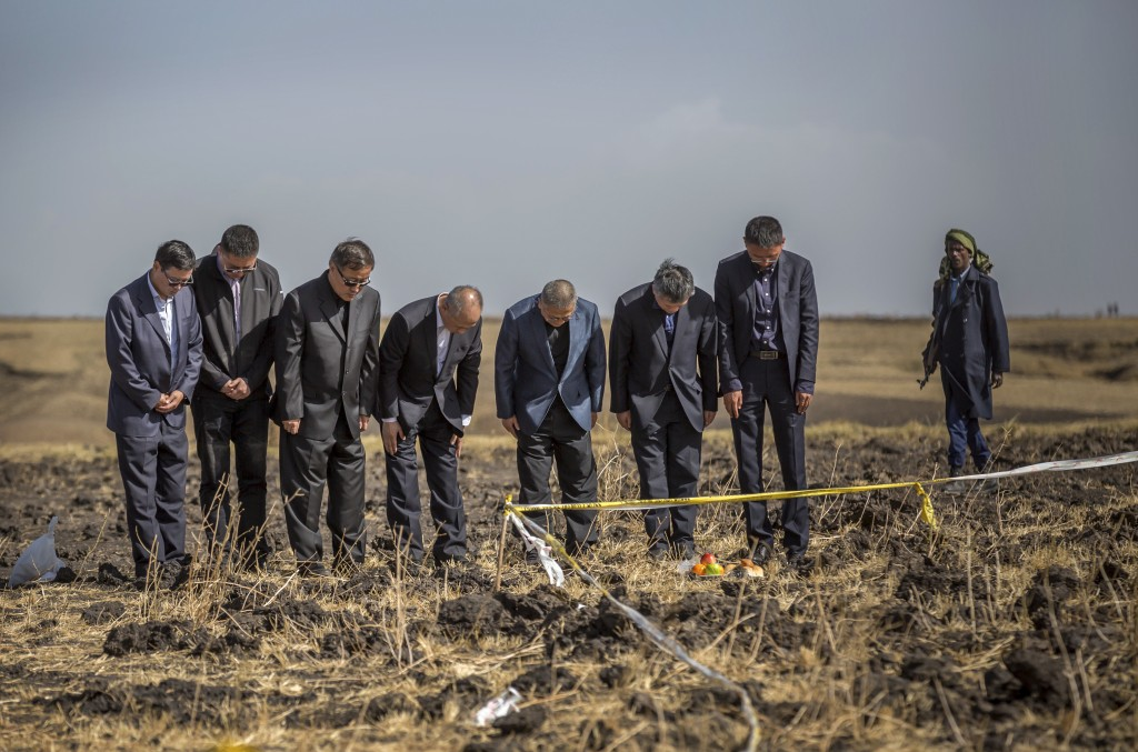 FILE - In this Tuesday, March 12, 2019 file photo, officials from the Aviation Industry Corporation of China (AVIC) pray next to an offering of fruit,...