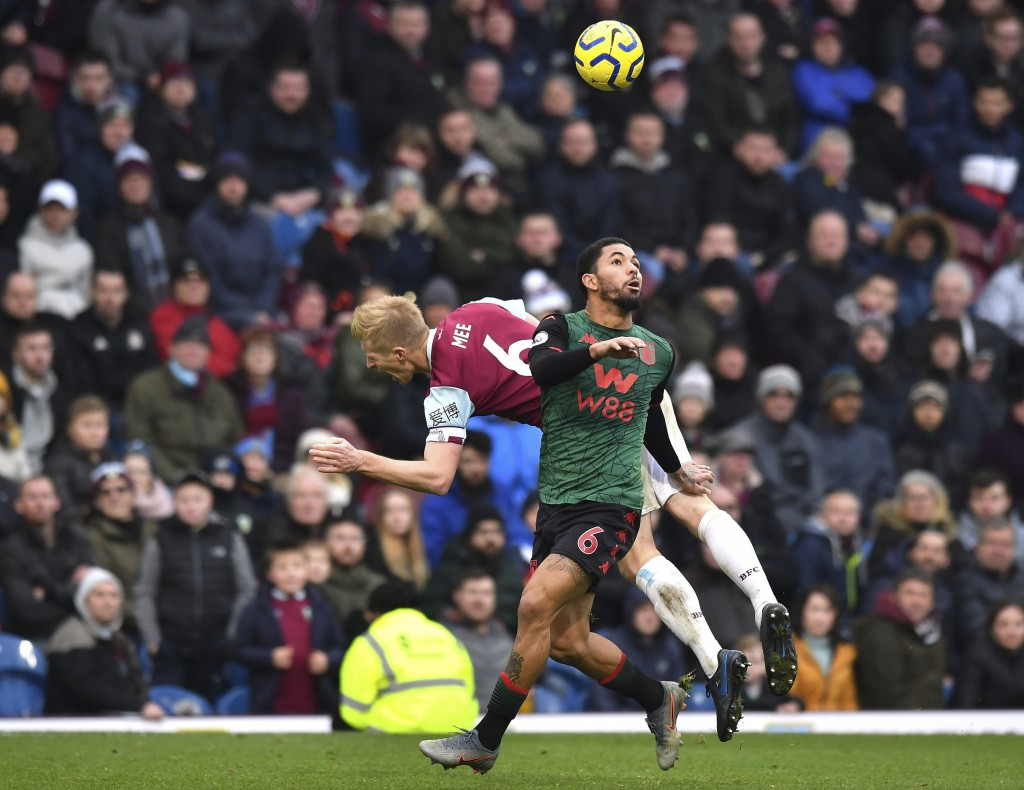 Burnley's Ben Mee, background and Aston Villa's Douglas Luiz battle for the ball, during the English Premier League soccer match between Burnley and A...