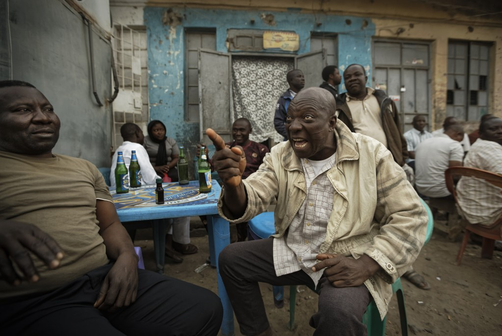 FILE - In this Feb. 16, 2019 fie photo, Nigerians engage in heated but friendly arguments about the postponement of the election, over beers at a stre...
