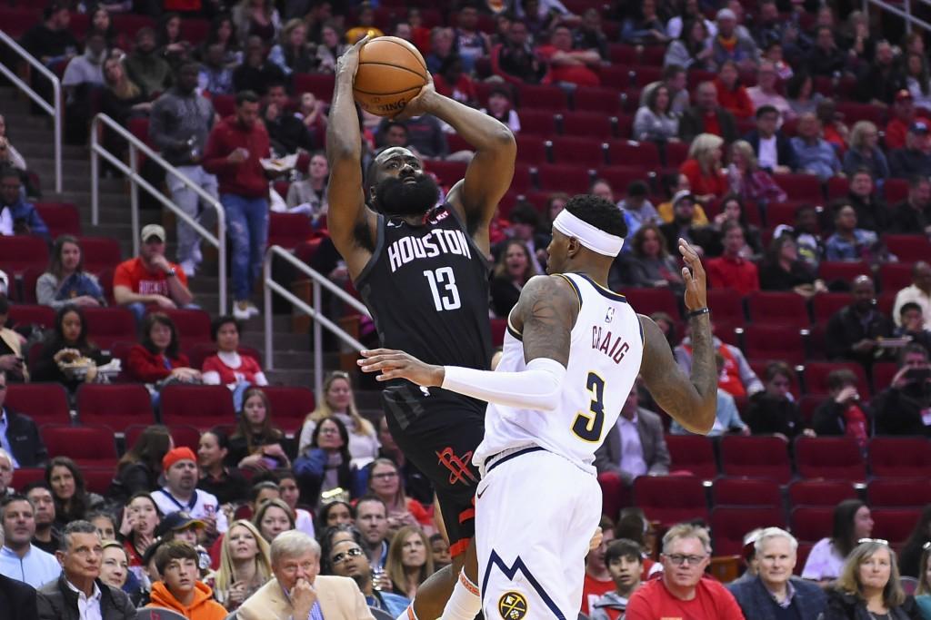 Houston Rockets guard James Harden (13) shoots as Denver Nuggets forward Torrey Craig defends during the second half of an NBA basketball game, Tuesda...