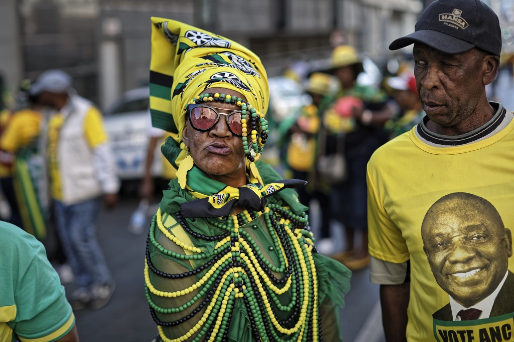 FILE - In this Sunday, May 12, 2019 file photo, a supporter of the African National Congress (ANC) party wears beads in the party colors, and another ...