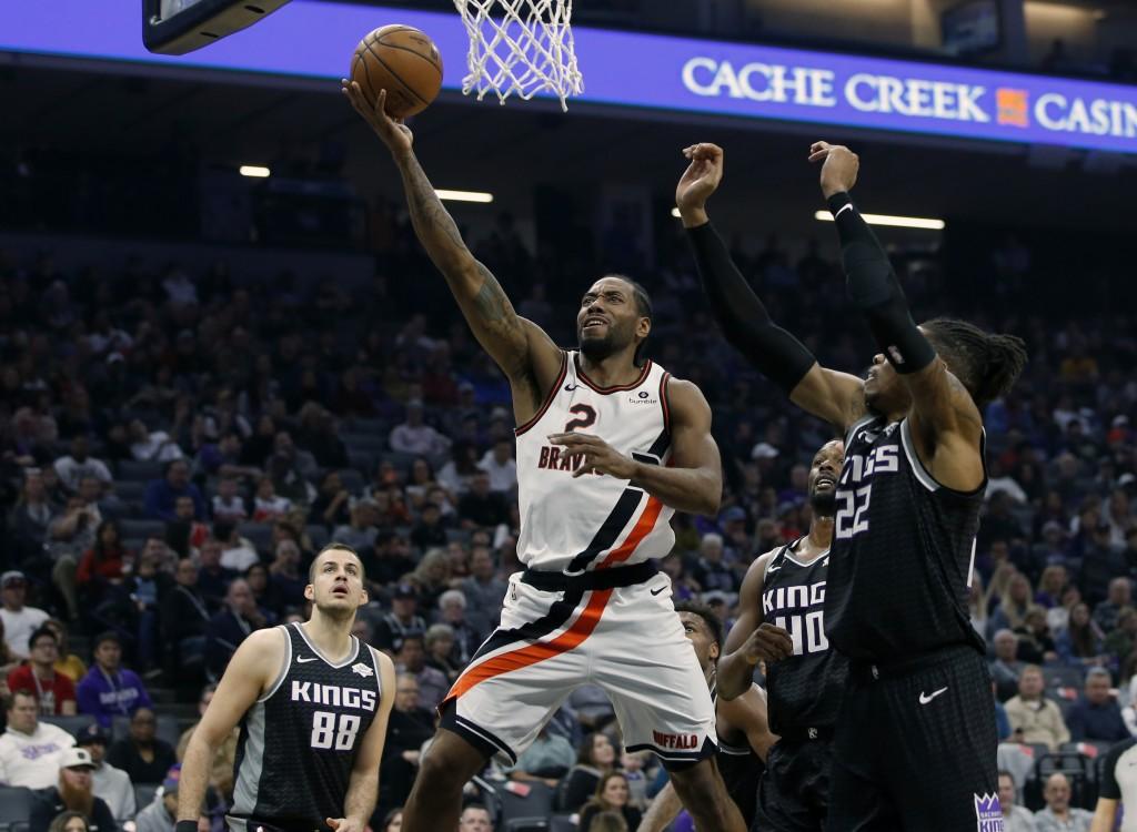 Los Angeles Clippers forward Kawhi Leonard, center, goes to the basket between Sacramento Kings' Nemanja Bjelica, left, Harrison Barnes and Richaun Ho...