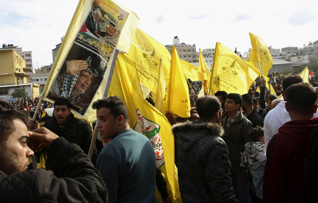 Palestinian supporters chant slogans and wave yellow Fatah flags and portraits of the late Palestinian President Yasser Arafat during a celebration ma...