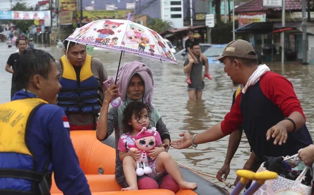 Rescue team talks to a girl through floodwaters at Jatibening on the outskirt of Jakarta, Indonesia, Wednesday, Jan. 1, 2020. Severe flooding hit Indo...