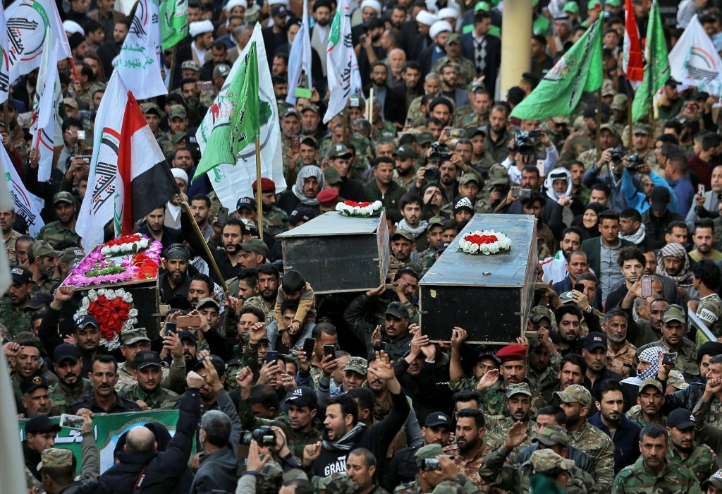 Mourners carry the coffin of Iran-backed Popular Mobilization fighters killed in the U.S. airstrike in Qaim, during their funeral in Najaf, Iraq, Tues...