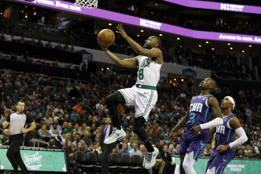 Boston Celtics' Kemba Walker (8) slips by for an easy two as Charlotte Hornets' Terry Rozier (3) and Devonte' Graham (4) trail in the paint during the...