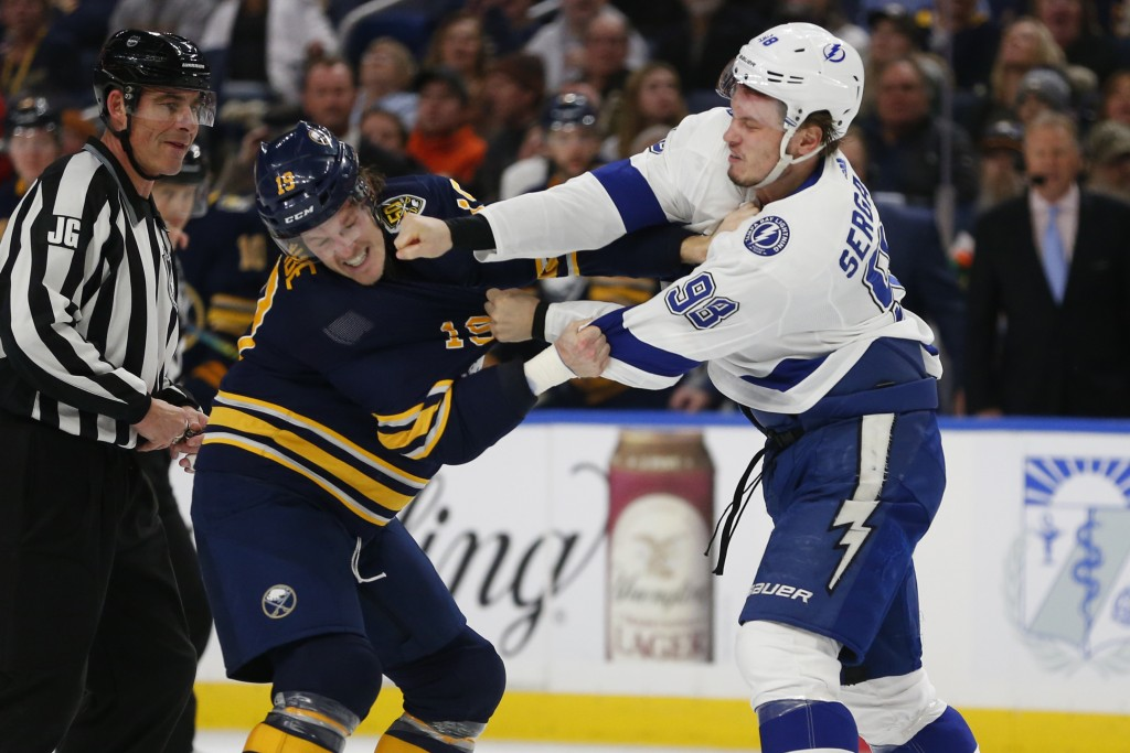 Buffalo Sabres defenseman Jake McCabe (19) and Tampa Bay Lightning defenseman Mikhail Sergachev (98) fight during the second period of an NHL hockey g...