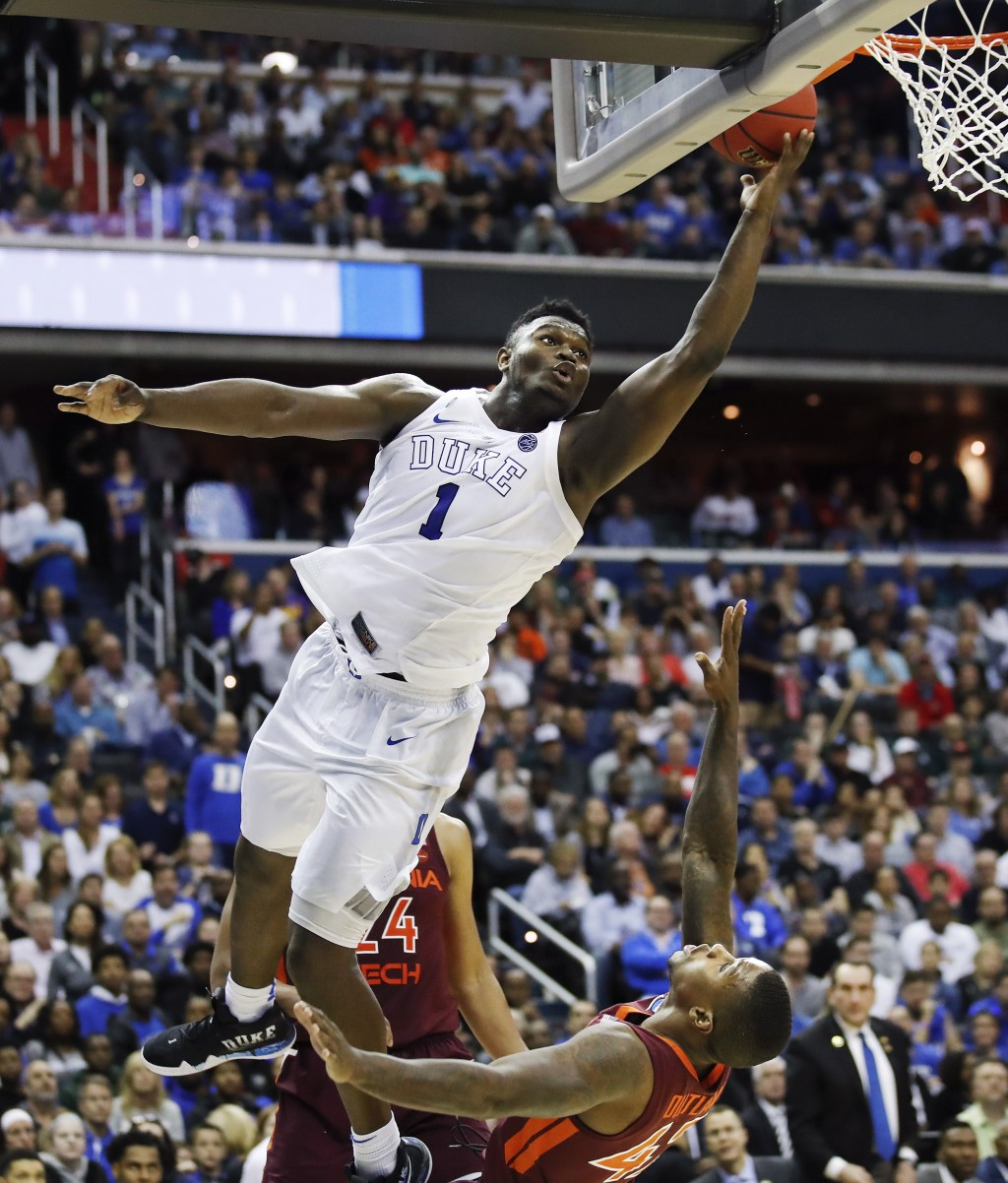 FILE - In this March 29, 2019, file photo, Duke forward Zion Williamson (1) drives to the basket to score over Virginia Tech's guard Ty Outlaw (42) du...