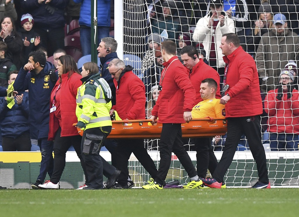 Aston Villa goalkeeper Tom Heaton, centre, is carried off the pitch on a stretcher, during the English Premier League soccer match between Burnley and...