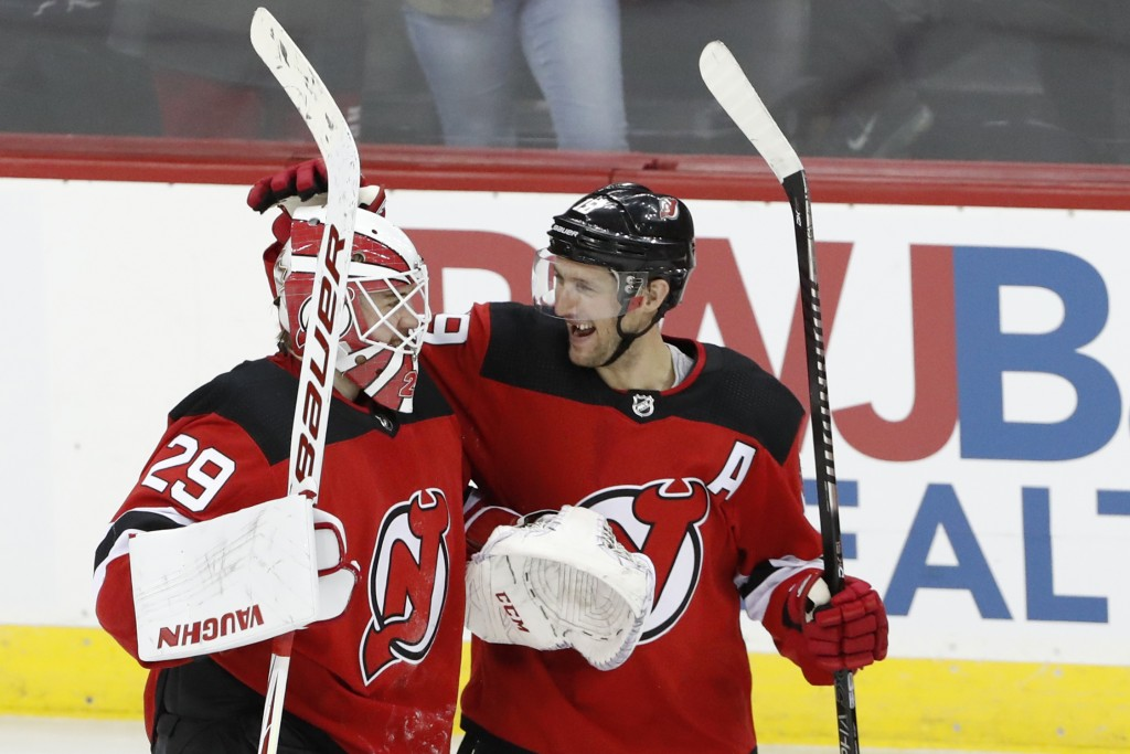New Jersey Devils center Travis Zajac (19) celebrates with Devils goaltender Mackenzie Blackwood (29) after the Devils defeated the Boston Bruins in a...