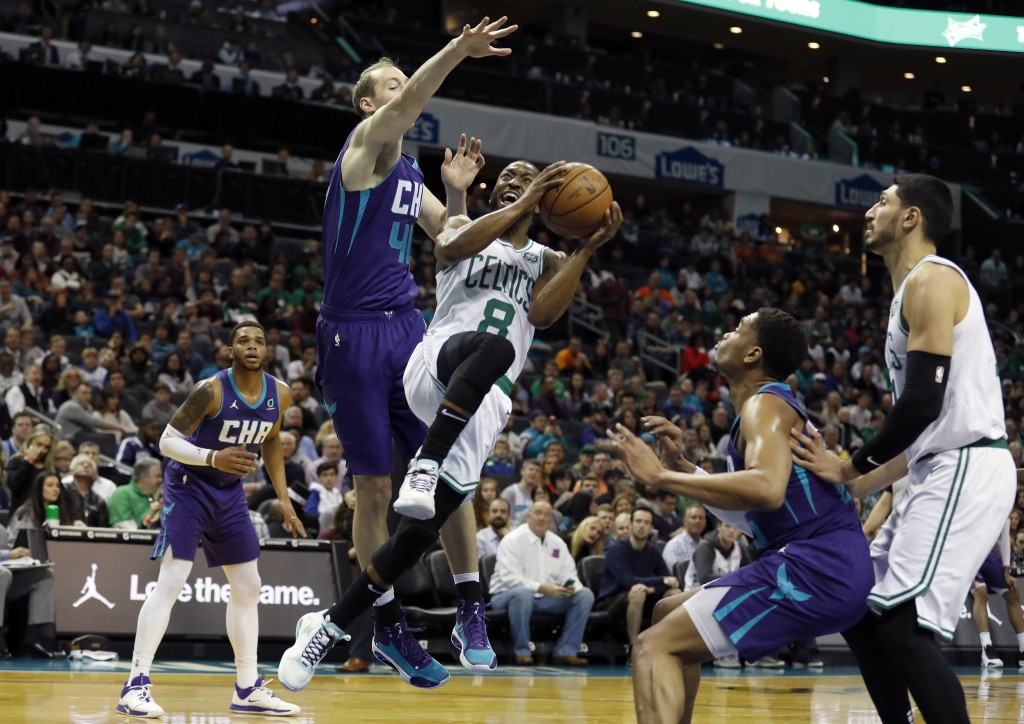 Boston Celtics' Kemba Walker (8) makes a move to try and shoot past Charlotte Hornets' Cody Zeller (40) during the first half of an NBA basketball gam...