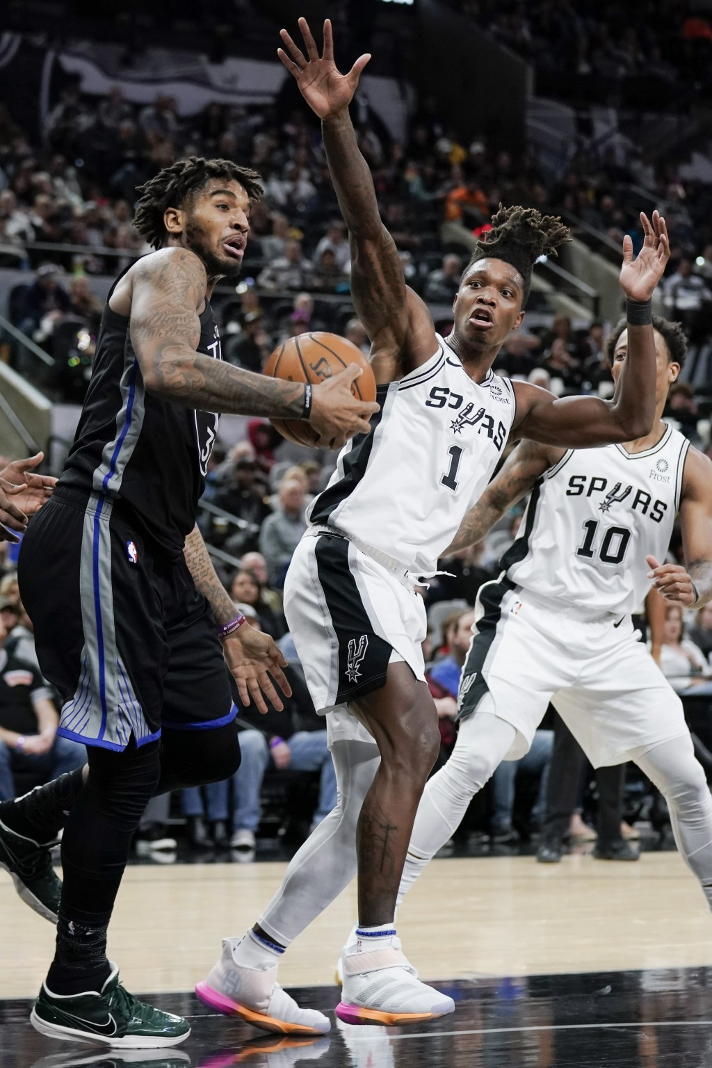 Golden State Warriors' Marquese Chriss, left, tangles with San Antonio Spurs' Lonnie Walker IV (1) during the first half of an NBA basketball game, Tu...