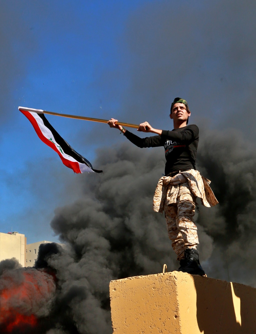 Protesters burn property as a militiaman waves an Iraqi flag in front of the U.S. embassy compound, in Baghdad, Iraq, Tuesday, Dec. 31, 2019. Dozens o...