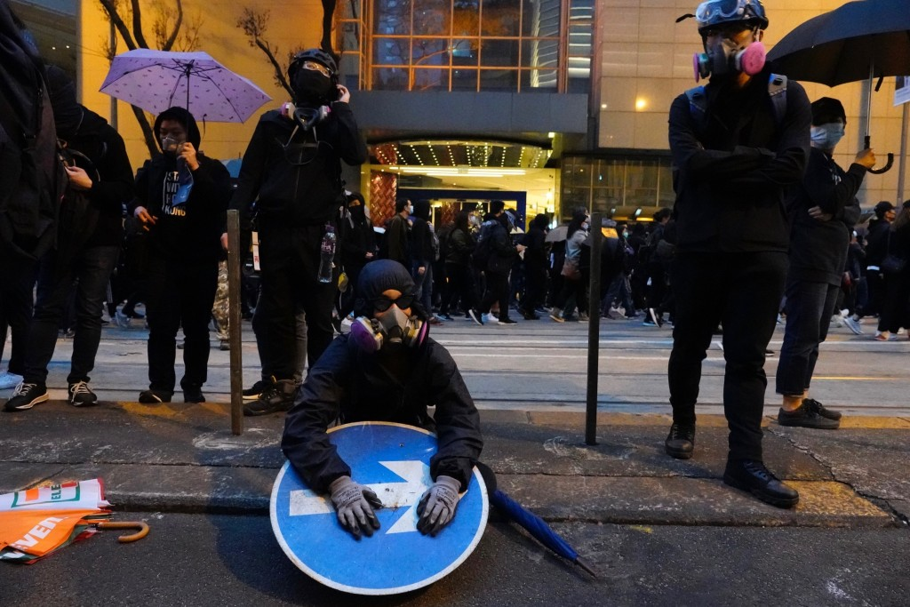 A group of protestors take rest as others march behind in Hong Kong, Wednesday, Jan. 1, 2020. Hong Kong toned down its New Year's celebrations amid th...